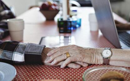 Äldre kvinna håller hand med man hemma